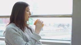 Den unga kvinnan dricker nytt sammanpressad fruktsaft i ett kafé som ut ser fönstret lager videofilmer