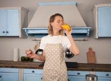 Den unga kvinnan dricker orange fruktsaft och smakar kakan som hon har gjort i hennes kök royaltyfri bild