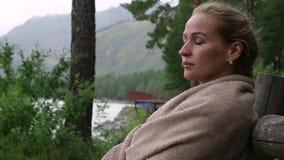 Den unga kvinnan dricker varmt kaffe eller te nära bergfloden Lugna och hemtrevlig tid i bergsemesterort stock video
