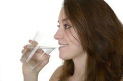 Den unga kvinnan dricker vatten Arkivfoton