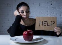 Den unga kvinnan eller tonårig seende äpplefrukt på maträtt som symbol av galet bantar i näringoordning Royaltyfri Foto