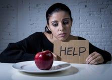 Den unga kvinnan eller tonårig seende äpplefrukt på maträtt som symbol av galet bantar i näringoordning Royaltyfria Foton