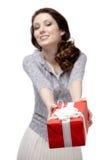 Den unga kvinnan erbjuder en gåva Royaltyfria Bilder