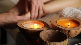 Den unga kvinnan får en fotmassage i brunnsortsalongen stearinljus stänger sig upp stock video