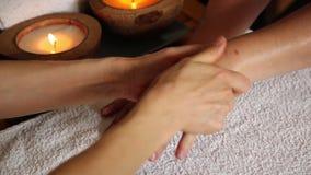 Den unga kvinnan får en handmassage i brunnsortsalongen stearinljus stänger sig upp massörarmglidbana på den kvinnliga handen lager videofilmer