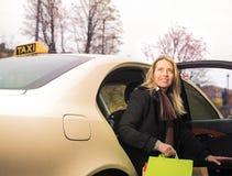 Den unga kvinnan får ut ur taxien med shoppingpåsar arkivfoton