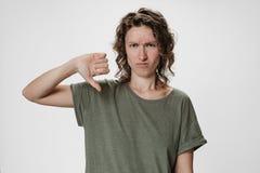 Den unga kvinnan för lockigt hår rynkar pannan framsidan, har misshagit ger tummen ner gest royaltyfri fotografi