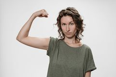 Den unga kvinnan för lockigt hår visar muskeln på hennes hand, känner sig stolt att vara stark royaltyfri bild