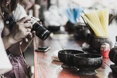 Den unga kvinnan förbereder en kamera som är klar att ta ett foto på flodstranden Arkivbilder
