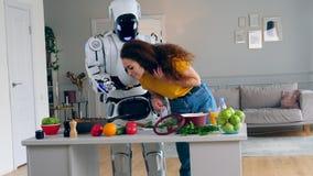 Den unga kvinnan försöker mat som lagas mat av en cyborg lager videofilmer