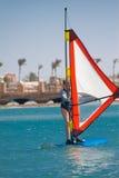 Den unga kvinnan faller av brädet för att vindsurfa i Egypten, Hurgha Arkivfoton