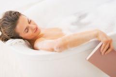 Den unga kvinnan faller sovande medan läseboken i badkar Arkivbilder
