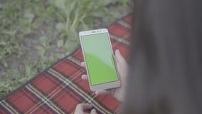 Den unga kvinnan fingrar maskinskrivning på hennes smartphone lager videofilmer