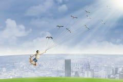 Den unga kvinnan flyga iväg hållande fåglar Fotografering för Bildbyråer