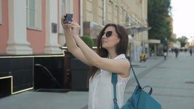 Den unga kvinnan fotograferar byggnad genom att använda telefonen, medan stå på gatan stock video