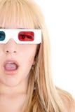 Den unga kvinnan förvånade hållande ögonen på TV med exponeringsglas 3D Royaltyfri Foto