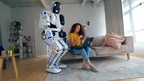 Den unga kvinnan fungerar en bärbar dator och konsulterar en cyborg lager videofilmer