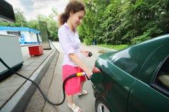 Den unga kvinnan fyller bensinbilen Arkivfoton