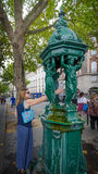 Den unga kvinnan fyller upp den plast- flaskan på en offentlig vattenspringbrunn i Paris Arkivbilder