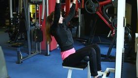 Den unga kvinnan går in för sportar, kondition på idrottshallen flicka som gör övningar på simulatorn arkivfilmer