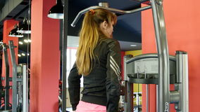 Den unga kvinnan går in för sportar, kondition på idrottshallen flicka som gör övningar på simulatorn stock video
