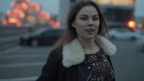 Den unga kvinnan går i aftonstaden stock video