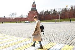 Den unga kvinnan går i staden på den röda fyrkanten royaltyfri bild