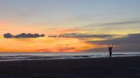 Den unga kvinnan går lyckligt vid kusten på en härlig solnedgång arkivfilmer