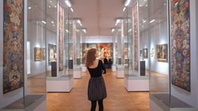 Den unga kvinnan går mellan utställningar och konstverk i ett museum eller en Art Gallery arkivfilmer