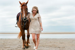 Den unga kvinnan går nära en häst arkivfoto
