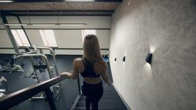 Den unga kvinnan går ner trappa till idrottshallen för utbildning inomhus arkivfilmer