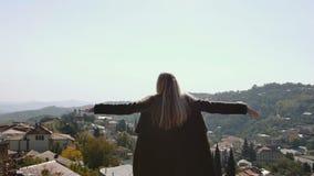 Den unga kvinnan går, och lyfta upp räcker att se byn och når en höjdpunkt fantastiskt landskap för bergbakgrund tillfredsställt lager videofilmer