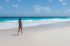 Den unga kvinnan går på en tom lös strand Arkivbilder