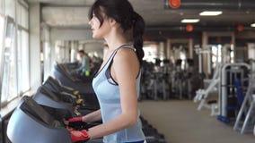 Den unga kvinnan går på en trampkvarn på idrottshallen cardio övningar i idrottshallen stock video