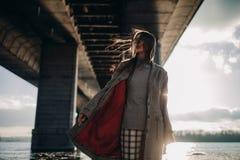 Den unga kvinnan går på flodbanken under bron på solnedgången royaltyfri fotografi