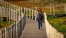 Den unga kvinnan går på strandpromenad royaltyfri fotografi