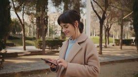 Den unga kvinnan går parkerar in med den smarta telefonen stock video