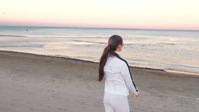Den unga kvinnan gör övningar för att återställa att andas på sandstranden på soluppgång i hösten, tillbaka sikt stock video