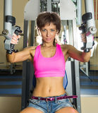 Den unga kvinnan gör övningar i idrottshall Royaltyfria Bilder