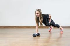 Den unga kvinnan gör övningar med vikt i idrottshall Royaltyfri Fotografi