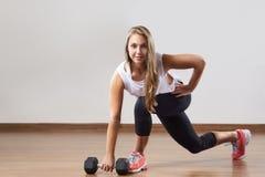 Den unga kvinnan gör övningar med vikt i idrottshall Arkivfoton