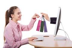 Den unga kvinnan gör beställning på datoren och får leverans Royaltyfri Bild