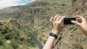 Den unga kvinnan gör ett foto av kanjonen i berg - Georgia arkivfilmer