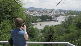 Den unga kvinnan gör fotoet av ropewayen, Georgia, Kutaisi arkivfilmer