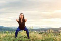 Den unga kvinnan gör genomkörare på naturen Sportkvinnaflicka utomhus Kvinnlig konditionflicka som gör sportövningar i sommartid  royaltyfria bilder