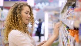 Den unga kvinnan gör köp i handelmitt arkivfilmer
