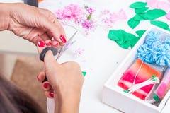 Den unga kvinnan gör konstgjorda blommor Royaltyfria Bilder
