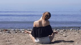 Den unga kvinnan gör meditation i lotusblomma att posera på havet/havstranden, harmoni och begrundande Praktiserande yoga för här arkivfilmer