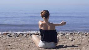 Den unga kvinnan gör meditation i lotusblomma att posera på havet/havstranden, harmoni och begrundande Praktiserande yoga för här lager videofilmer