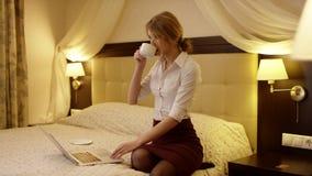 Den unga kvinnan gör något i en anteckningsbok och dricker en kopp te lager videofilmer